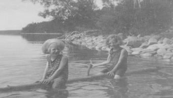 Red Deer Archives, P5687; Two girls on a log on Sylvan Lake, ca. 1920