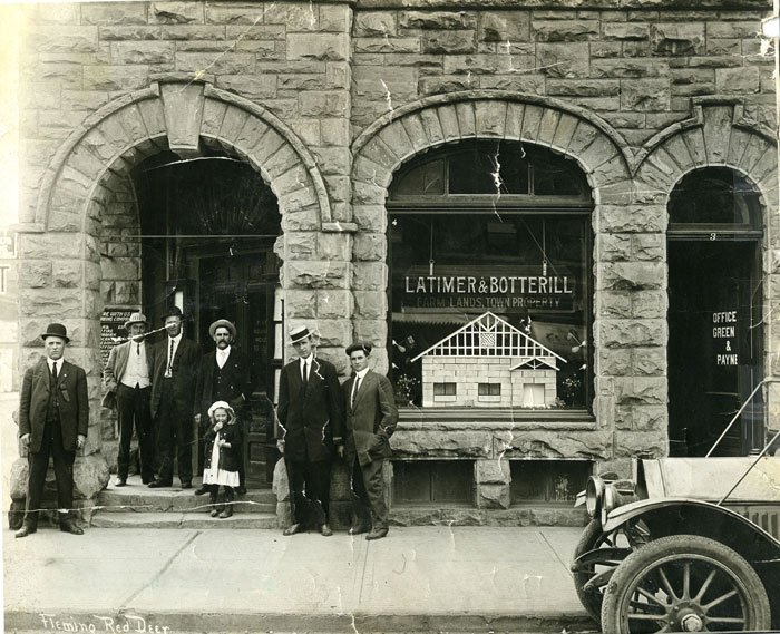 A group of men and a child standing outside a building downtown Red Deer in 1909.