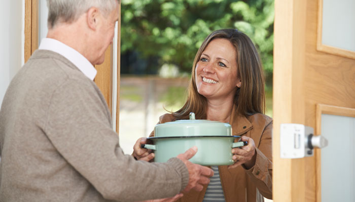photo of a woman passing a man a casserole dish