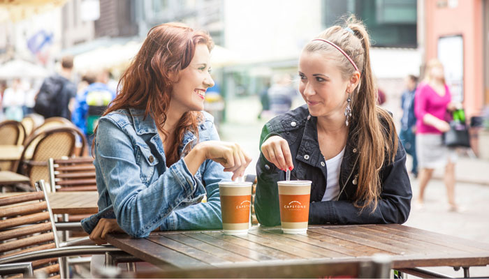 Two women sitting at an outside table enjoying coffees