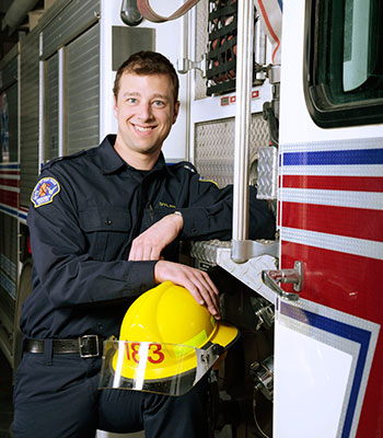 A City of Red Deer Firemedic standing in uniform next to a firetruck
