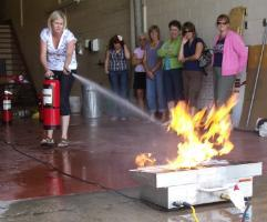 Image of a woman taking fire Extinguisher Training