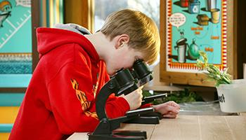 Child with microscope on Waste Management Facility Tour