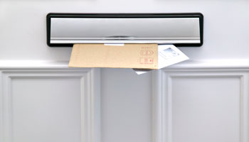image of mail coming through mail slot in the door