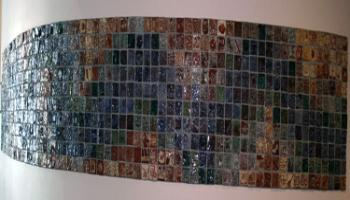 Entire wall filled with square tiles created by children in various colors, each tile has a different picture.