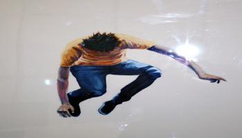 Painting of a man jumping in the air with a yellow shirt and blue jeans bent over at the waist appearing to look back down at the ground.