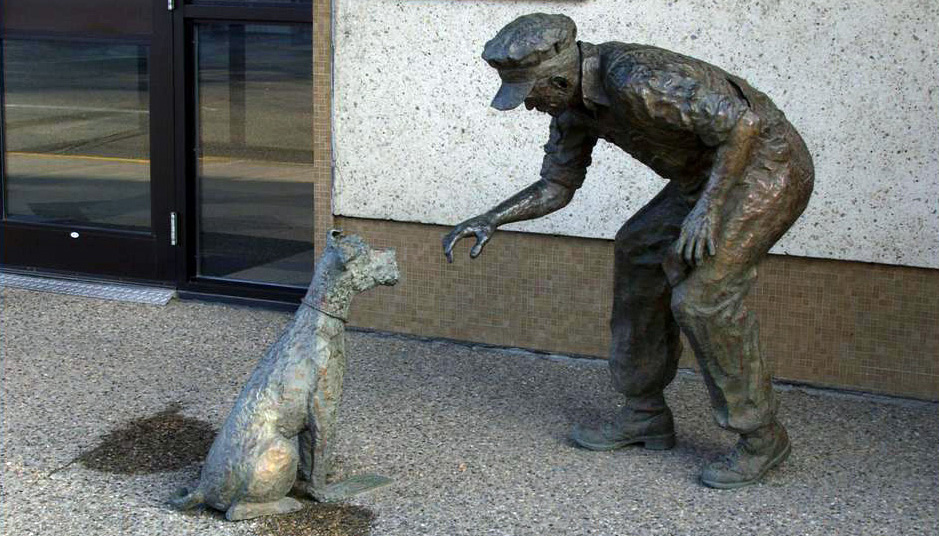 Bronze sculpture of a rail working confronting a little dog who is standing on the man's money.