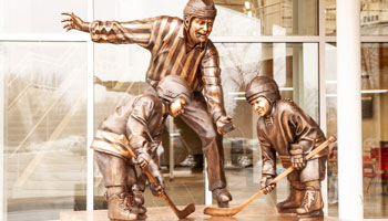 bronze sculpture of two young hockey players and a referee meeting for a face-off