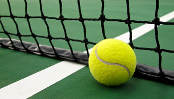 photo of tennis ball and net on a tennis court