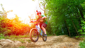 photo of teenage boy riding BMX bike in a treed area