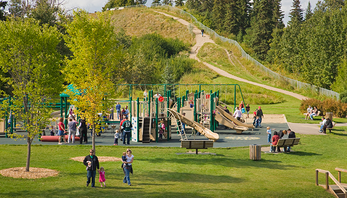Playground at Rotary Park with lots of families enjoying the amenity